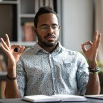 Calm African American man sit at desk meditating relieving negative emotions breathing fresh air, relaxed biracial male distracted from work practice yoga with mudra hands, stress free concept